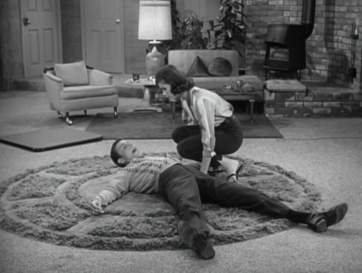 Laura finds Rob lying flat on the floor after he stumbles over one of Ritchie's toys. (Screen capture by Lindsey for TMP)