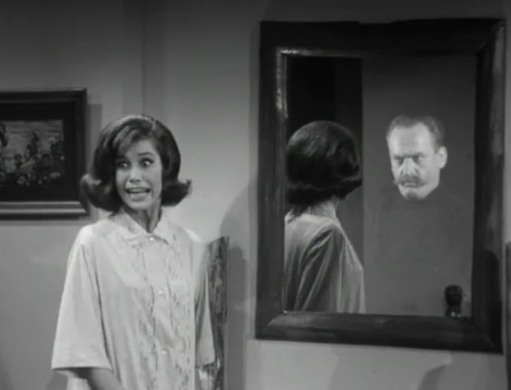 Laura is shocked to see a face other than her own staring back at her in the mirror! (Screen capture by Lindsey for TMP)
