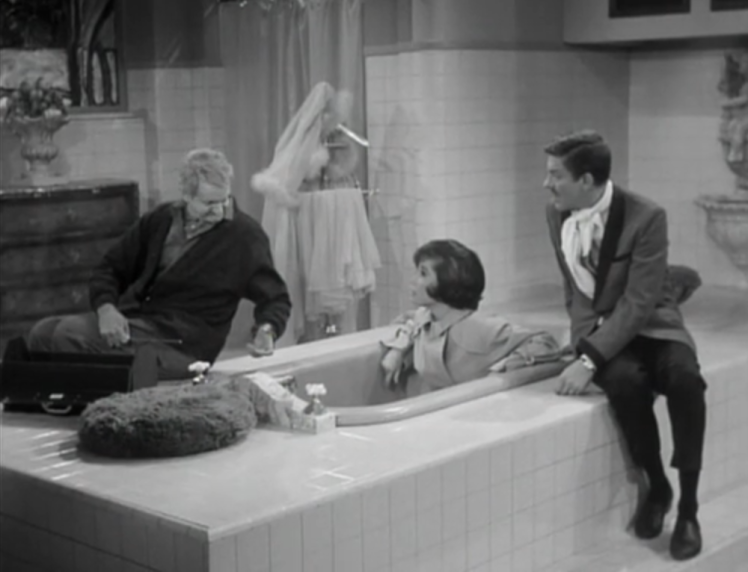 The hotel's elderly handyman tries to help Laura free her toe from the faucet. (Screen capture by Lindsey for TMP)