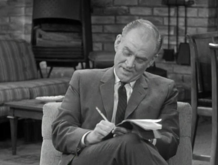 A reporter takes down notes on the crazy story of how Rob got his job. (Screen capture by Lindsey for TMP)