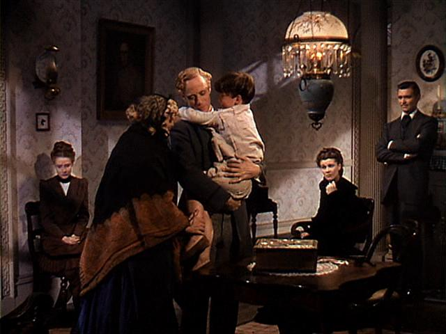 Mickey Kuhn is held by on-screen father Leslie Howard in one of his two scenes. (Image via vivienleigh.com)